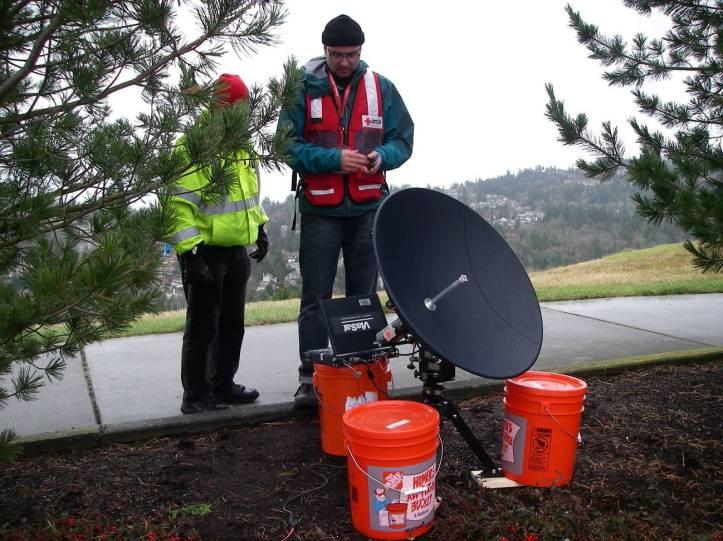 ViaSat dish setup with ballast buckets, with Dave Hersey, KE7PBA and John Carscadden, W7AFX.