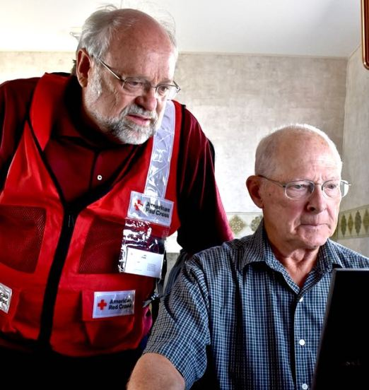 American Red Cross volunteer Bob Wallace looks over the shoulder of Kitchen Site Manager Dan Cenis to view images of the remains of Cenis' remote cabin that was destroyed by wildfire. Photo Credit: Lloyd Ziel/American Red Cross