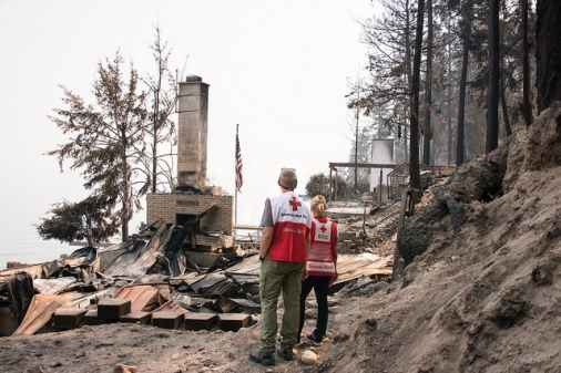 Red Cross Disaster Mental Health and Health Services volunteers Brett Wenger and Dawnda Smith view the remains of a home in Northeastern Washington that was completely destroyed by the wildfires. Photo Credit: Maggie Buckenmayer/American Red Cross