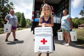 August 19, 2016. Denham Springs, Louisiana. Destiny, 8, helped carry a Red Cross clean-up kit to her home. (Her mom Hope and Aunt Linda are in the background). Photo by: Marko Kokic/American Red Cross