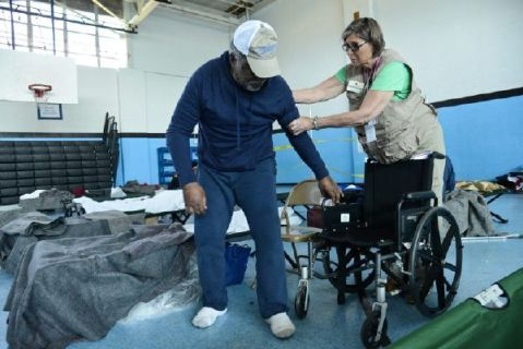 """Monroe, Louisiana. Annias Baker, 78, has lived in the Monroe, Louisiana, home he shares with his sister for 30 years, and this is the first time it has flooded. """"The water was all the way up to the bed,"""" he said. He and his sister evacuated to a Red Cross shelter nearly a week ago. Because health concerns make getting around difficult, Red Cross nurse Joan Nyitrai was able to provide him with a wheelchair to make his time away from home a little more comfortable. Photo by Daniel Cima/American Red Cross"""