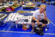 August 30, 2017. Delco Center Shelter, Austin, Texas. Gloria Montano of Victoria, Texas sits on her cot while making calls to family. Photo by Chuck Haupt for the American Red Cross