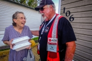 """September 3, 2017. Victoria, Texas. Red Cross volunteer Ted Mueller of Norwood, Colorado, brings hot meals to Mabel Gaines. Mabel said, """"The Red Cross is wonderful. God bless you."""" Photo by Chuck Haupt for the American Red Cross"""