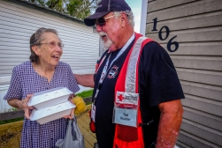"September 3, 2017. Victoria, Texas. Red Cross volunteer Ted Mueller of Norwood, Colorado, brings hot meals to Mabel Gaines. Mabel said, ""The Red Cross is wonderful. God bless you."" Photo by Chuck Haupt for the American Red Cross"