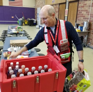 Red Cross volunteer places beverages on a table in a shelter.