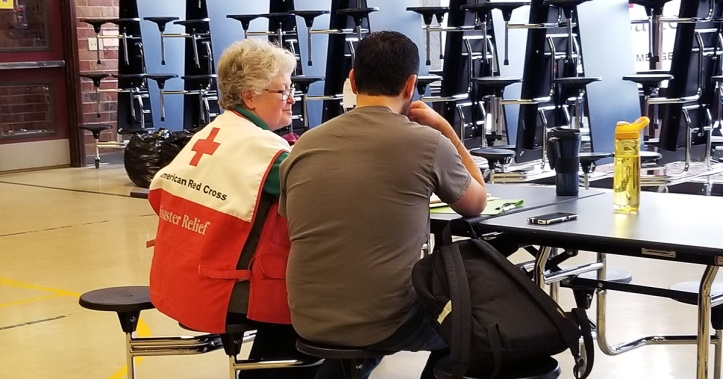 Red Cross volunteer sits next to a man at a table in a shelter.