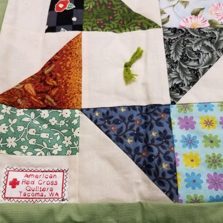 quilt with red cross stitching