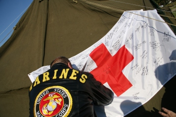 A veteran signs an American Red Cross flag at the Service to the Armed Forces tent on the National Mall.