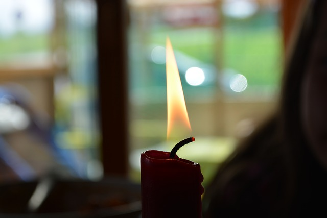 Photo of the top of a candle that is lit. Background is blurred and appears to show a person who is partially cropped from the photo and a window behind the person.