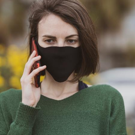 Woman wearing mask holds phone to her ear.