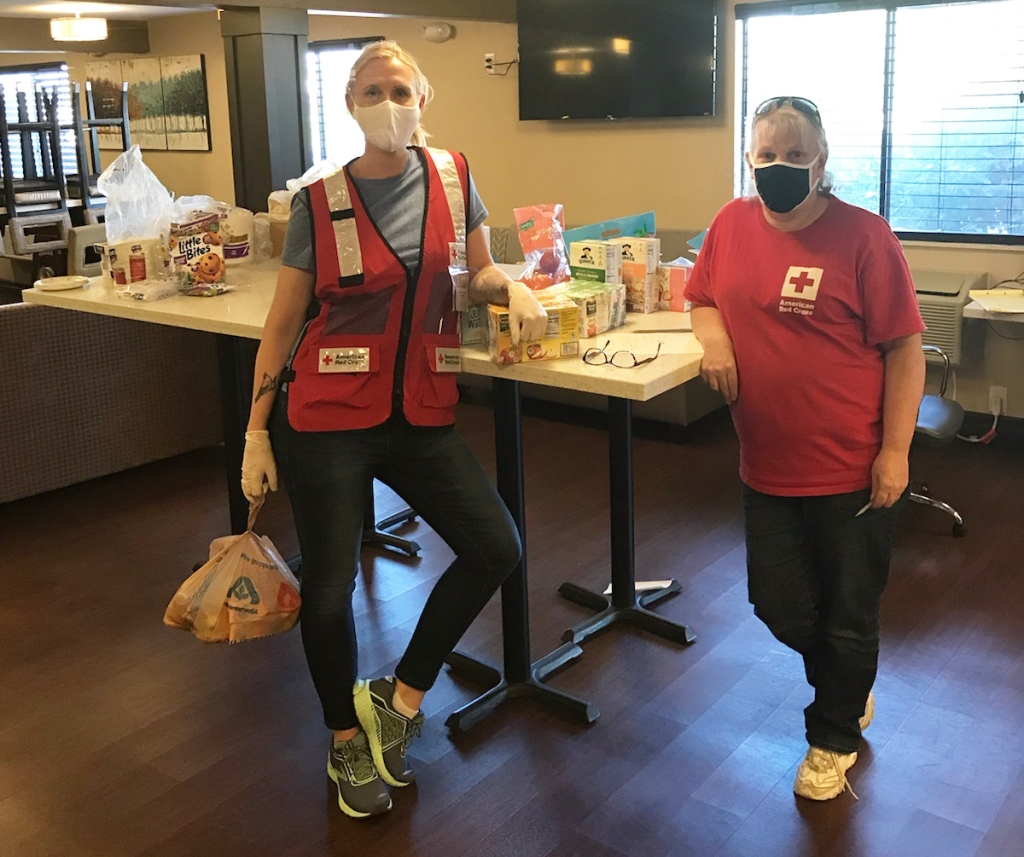 Photo of two red cross volunteers wearing masks standing in a kitchen in front of a counter that has pantry food items on it. The volunteer on the left is Kate and the volunteer on the right is Tracy Sheehy.