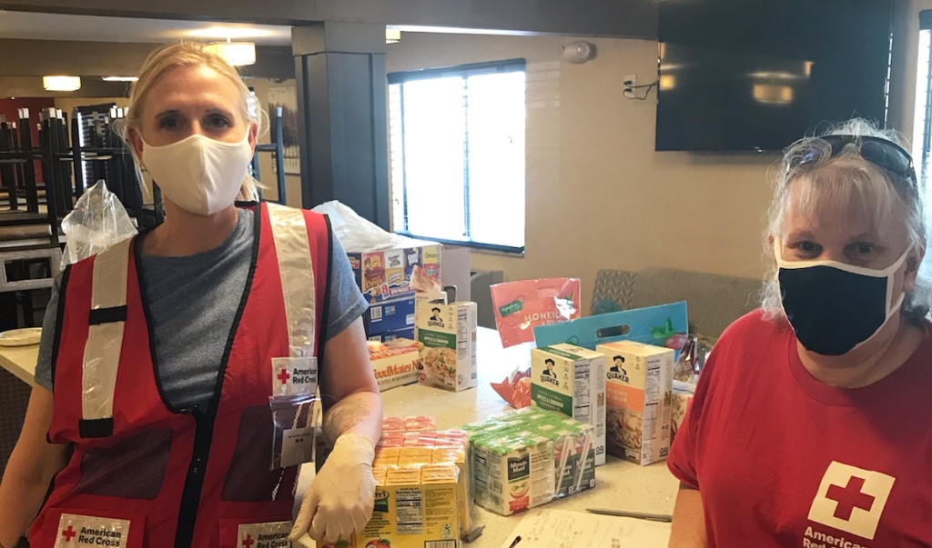 Close up photo of two red cross volunteers wearing masks standing in a kitchen in front of a counter that has pantry food items on it.